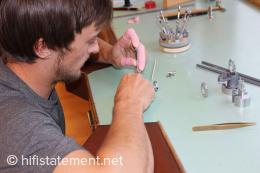 Daniel Schmied montiert Lager an einem Uhrmachertisch mit den charakteristischen gepolsterten Armauflagen