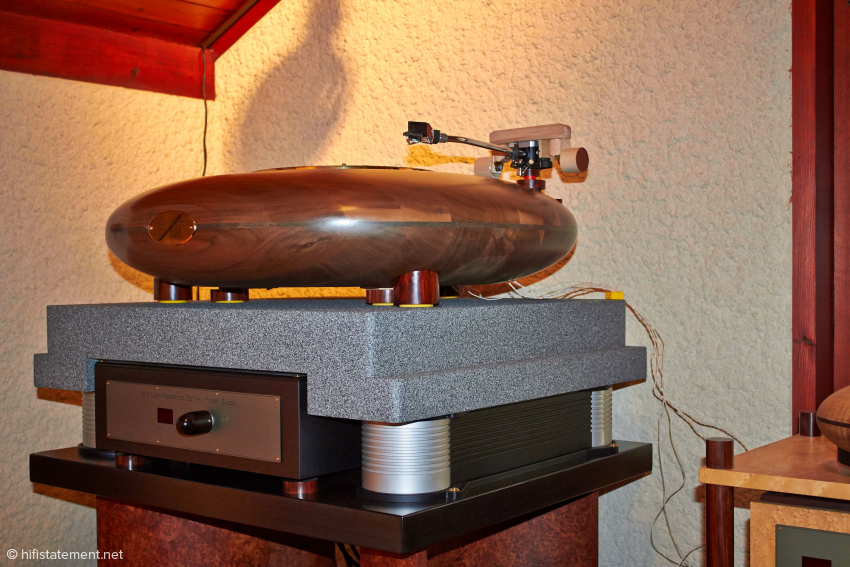 Here, on its throne, the UFO mothership - 85 cm in diameter! Uh, perhaps I should have brought along the Klingon Disruptor just to be on the safe side. Anyway, the turntable sits on vibration dampers from the company Accurion, who normally builds such bases for electron microscopes. By switching off the control you could slightly notice that the reproduction becomes unclear and the bass a little muddier. Relatively speaking. Schmidlin could not keep his fingers away from the tonearm. In his basement he has done some passionate testing and modifying and we find a completely new and entirely custom designed tonearm. The man is probably never totally satisfied with any outcome.