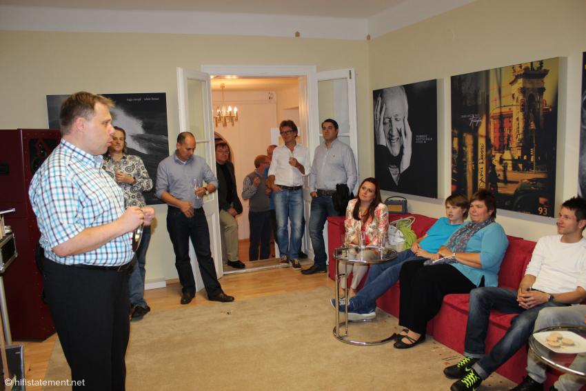 Volker Lange (links) begrüßt einen Teil seiner Gäste im Hörraum. Die Cover-Reproduktionen an den Wänden sind Absorber von Fast Audio