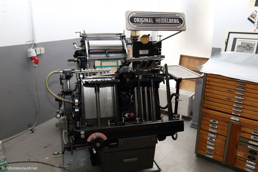 Ein klassische Druckmaschine. Daneben der Schrank mit den Schriften