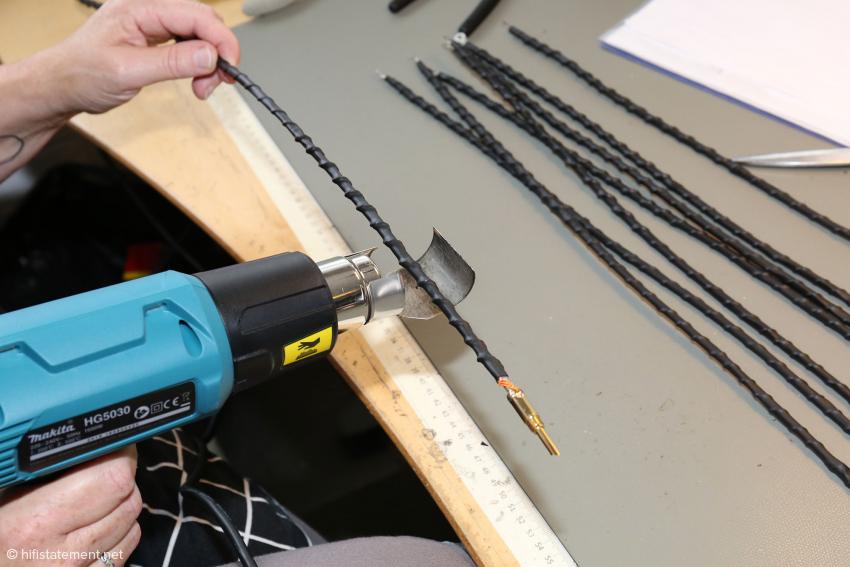 Teilstücke eines Lautsprecherkabels werden mit einem Schrumpfschlauch überzogen
