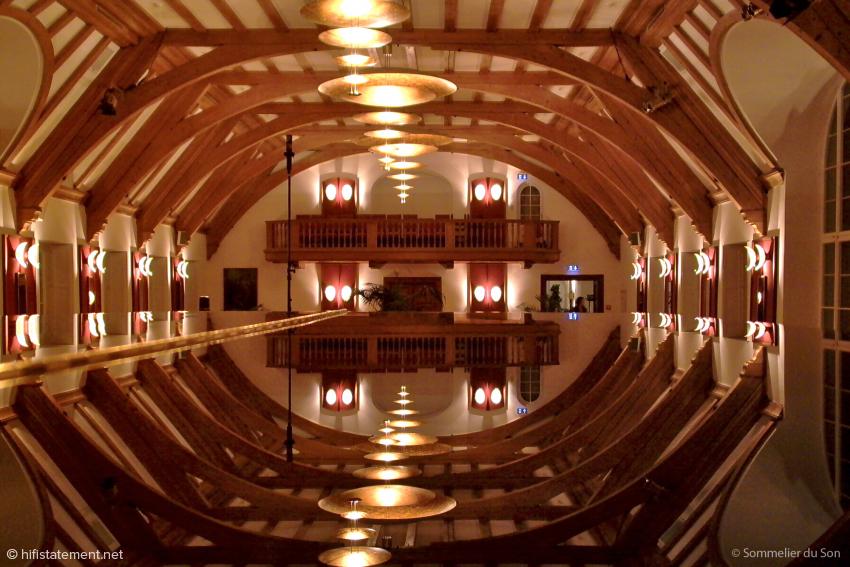 Kein Photoshop, sondern Realität: Leuchten und Deckenstruktur des großes Saales in Schloss Elmau spieglen sich im Deckel des Steinway