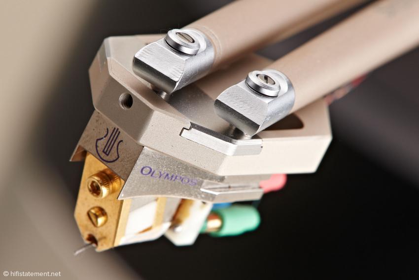Das linke Aluminiumrohr erfüllt die Funktion eines üblichen Tonarmrohres. Das rechte Alurohr verändert den Kröpfungswinkel des Headshells. Nach dem Lösen der in der mittigen Bohrung verborgenen Madenschraube lässt sich der bronzefarbene Systemträger vom Miniatur-Headshell abziehen