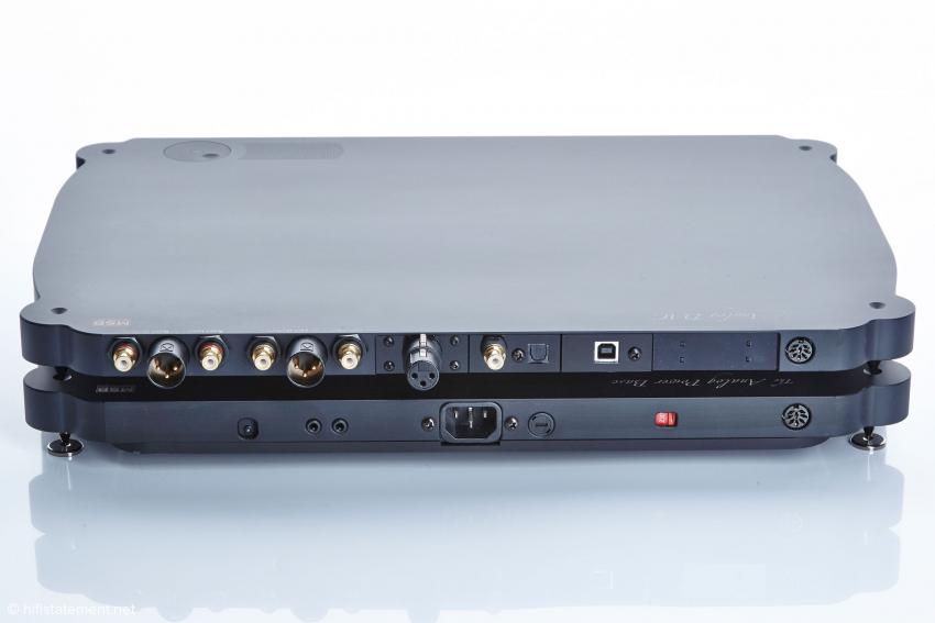 Die Rückseite des Netzteils unten weist als Bedienungselement links unten einen kleinen Netzschalter auf. Dieser leuchtet stets, sobald das Gerät am Netz ist,  entweder rot im Standby oder grün, wenn der DAC mit Strom versorgt wird. Der Wandler bietet-Cinch-Ein- und Ausgänge und dazwischen die pegelgleichen XLR-Ausgänge. Weiterhin gibt es ein AES/EBU, ein SPDIF- ein Toslin- und ein USB-Eingangsmodul; der freie Platz rechts ermöglicht die Aufnahme des RS-232 Moduls für WiFi. Ganz rechts die Verbindungs-Buchse zum Netzteil