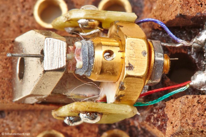 Hier ist der kreuzförmige Spulenträger mit seinen Wicklungen sehr gut zu sehen. Laut Produktinformation bestehen sie aus Golddraht. Sollte nur die Isolierung dafür verantwortlich sein, dass das Material hier wie Kupfer wirkt?