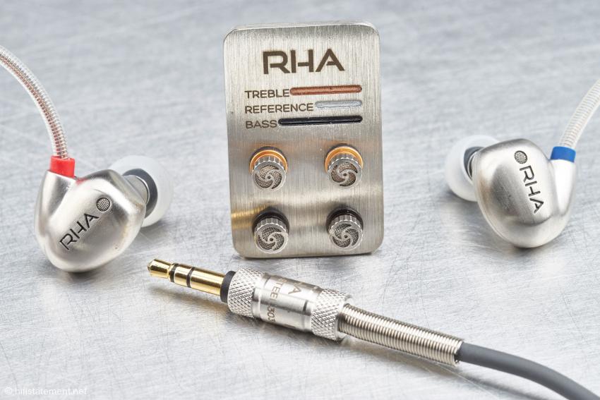 Die zwei deutlich für das linke und rechte Ohr gekennzeichneten Hörer aus Edelstahl flankieren hier das kleine Board, auf dem die zwei nicht genutzten Paare der Tuning-Filter zur Aufbewahrung eingeschraubt werden. Gut zu sehen sind die entsprechenden Farb-Codierungen. Hier fehlt das Reference-Filter, das an den Hörern im Einsatz ist
