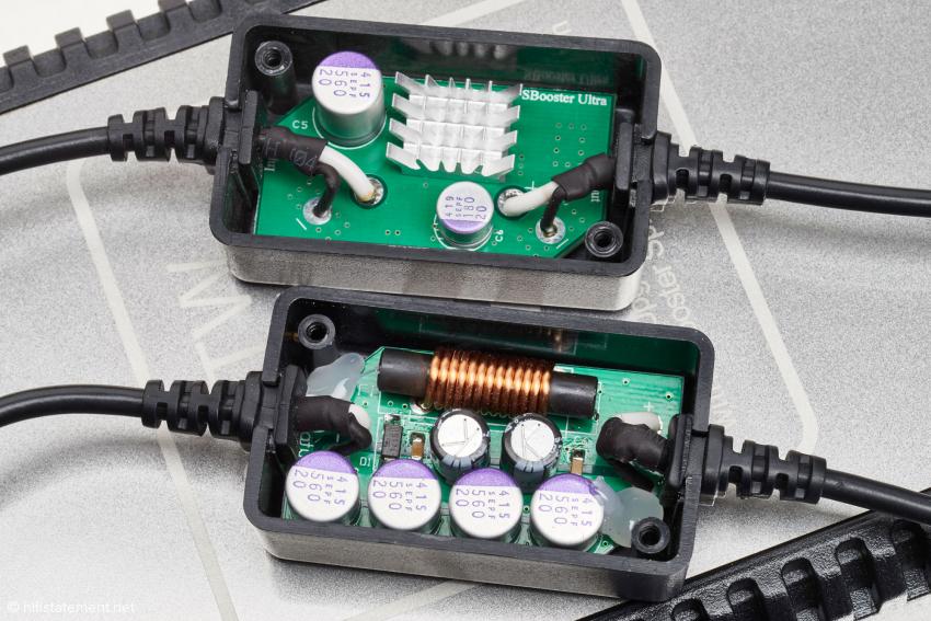 Der Blick in die zwei Black-Boxes, die sich im Kabelweg befinden. Fest im Kabel installiert ist die untere, die für Leistungspeaks Reserven bereithält. Der SBooster Ultra Filter oben eliminiert Störungen im Netz und ist im Kabel steckbar