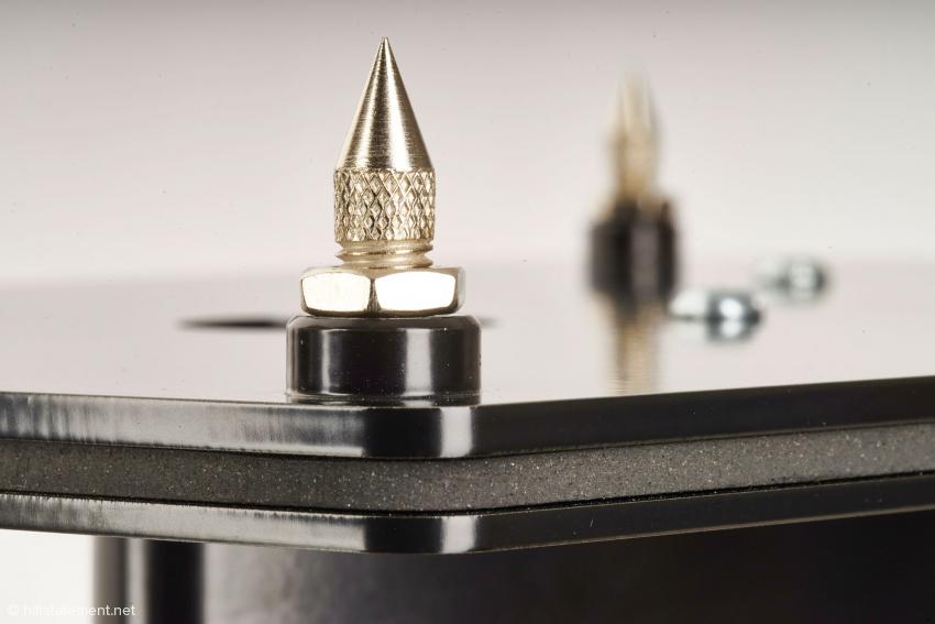Die Spikes nehmen unüberhörbar Einfluss auf die Präzision des Klanges. Um den Fussboden muss man nicht fürchten. Schonende Metallplättchen liegen bei. Deutlich zu erkennen ist der Sandwich-Aufbau der Ständerbasis. Zwischen den zwei Stahlplatten befindet sich eine Lage absorbierenden Materials