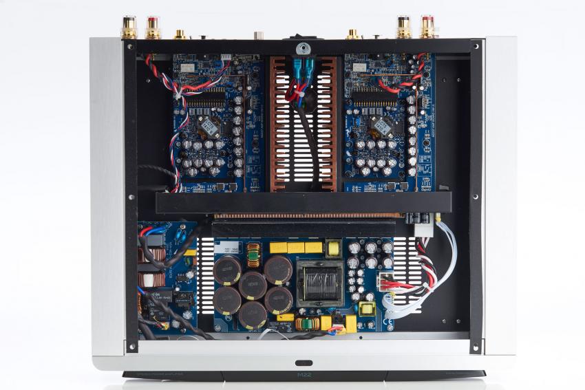 Der akkurate Aufbau der Masters M22: Die Hypex-Module sind am oberen Gehäuserand zu sehen. Der ovale Taster auf der massiven Aluminium-Front am oberen Bildrand schaltet den Verstärker aus dem Standby-Modus in den Spielbetrieb oder umgekehrt, falls die Einschalt-Automatik nicht genutzt wird. Auch die M22 hat rückseitig einen harten Netzschalter