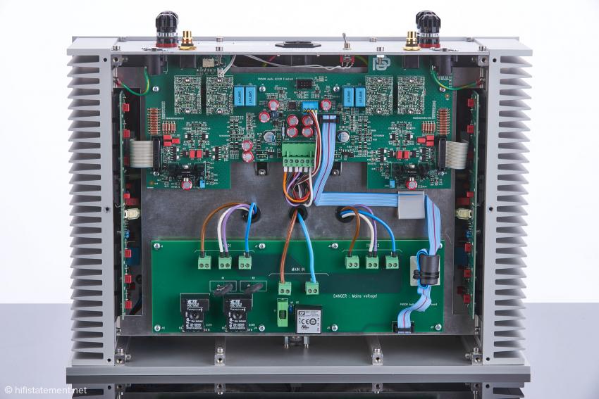 Blick in die Phison Audio Endstufe A2.120: Unterhalb der Platine vor den Vorstufenteil verbergen sich zwei 500-Watt-Ringkerntrafos und die Ladeelkos; auf den seitlichen Kühlkörpern sind jeweils sieben Leistungstransistoren montiert