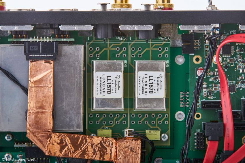 Die beschrifteten Lundahl-Übertrager nehmen sich des Signals der Analog-Eingänge an. Das mit Kupferfolie geschirmte Kabel verdeckt den Raum zwischen den beiden darunter liegenden größeren Lundahl-Übertragern, die für die Strom/Spannungs-Wandung nach den DAC-Chips zuständig sind