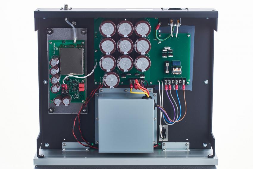 Innenansicht der Master-Clock: in der Mitte unten der gekapselte Trafo, darüber Gleichrichtung und Siebkapazitäten, links die Clock-Einheit