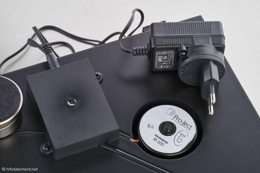 Das Steckernetzteil speist die Regelelektronik für den extrem laufruhigen und sehr gut entkoppelten Motor. Die Umschaltung zwischen 33⅓ und 45 Umdrehungen pro Minute erfolgt elektronisch