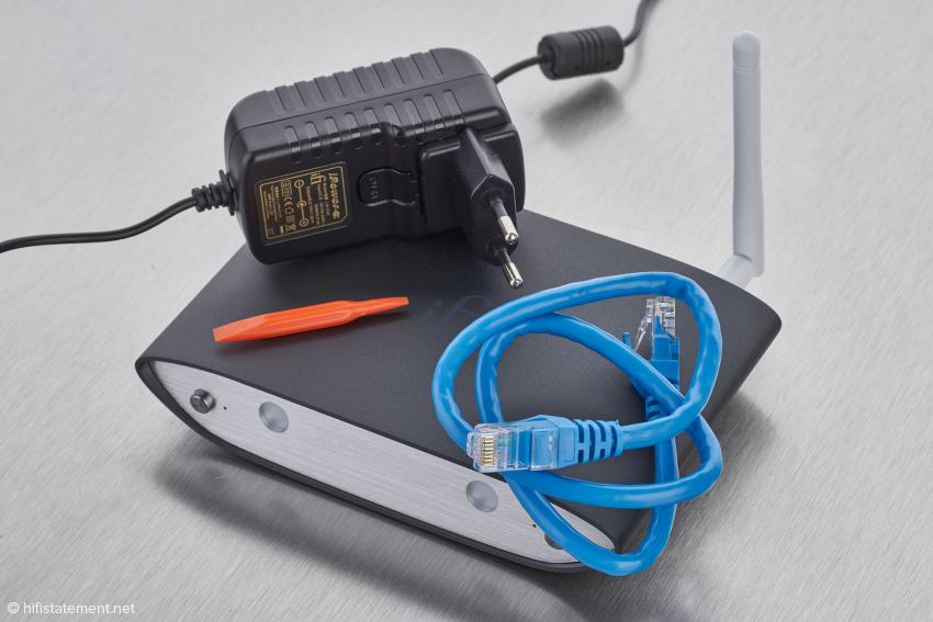 Der Lieferumfang besteht aus Netzteil, WLAN-Antenne, kurzem LAN-Kabel und einem Einstell-Hilfsmittel